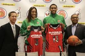 Indiana standout Taya Reimer, and Four-time Illinois state champion Jabari Parker hold up their McDonald's All American jerseys accompanied by Joe Wootten, left, the son of Morgan Wootten, and Douglas Freeland, right, Director of McDonalds All American Games after being picked as the national prep basketball players of the year Monday, March 18, 2013, in Chicago. The award, named for legendary Maryland high school coach Morgan Wootten, is awarded annually to the top male and female McDonald's All-American players. (caption provided by AP)